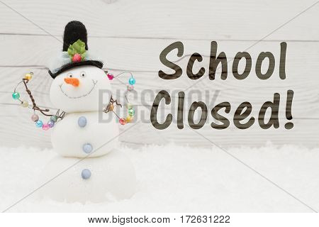 School canceled message A snowman with text School Closed on weathered wood