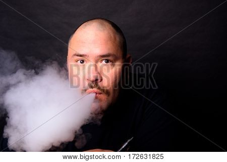 Older Adult Male Vaping In Low Key