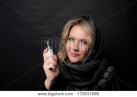 Low Key Image of a Woman in with a Scarf Vaping