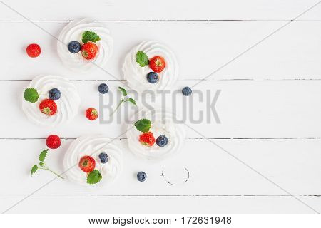 Meringues Pavlova cakes with strawberry and blueberry on wooden white background. Sweet dessert. Flat lay top view