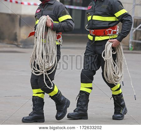 Two Firefighters With A Rope During The Rescue Operation