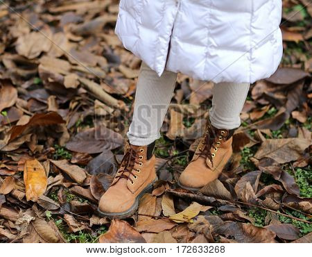 Winter leather boots of a little girl on the dry autumn leaves