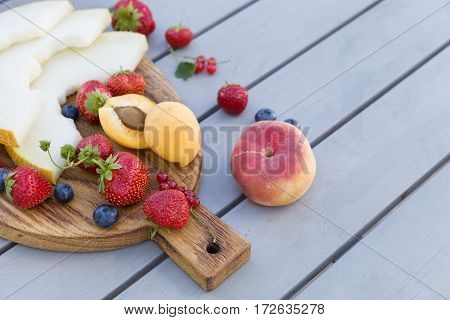 Wooden board with fresh organic fruit and berries: melon strawberries blueberries apricot peach and red current on grey background. Healthy snack