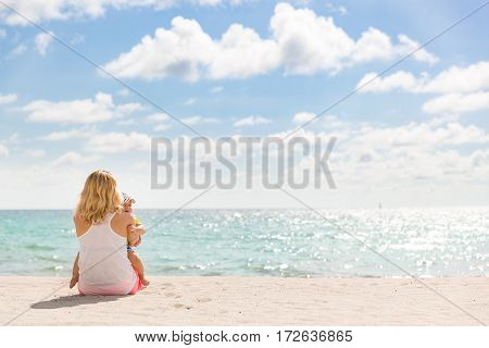 Back view on mother with a small adorable baby sitting on the sandy ocean beach. Family on vacations. Beautiful beach view. Woman with a child on the beach enjoying the sea view.