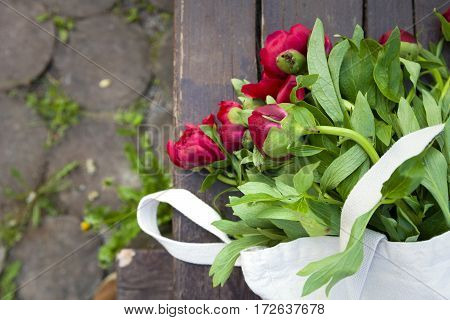 Top view on beautiful bunch of red peonies in textile bag on the wooden background. Flowers from market. Sunday market's flowers.