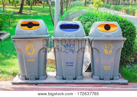 Different bins for collection of recycled materials in the park.