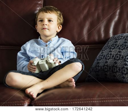 Boy Holiday Playing Game Sitting on Sofa at His Home