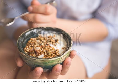 Young woman with muesli bowl. Girl eating breakfast cereals with nuts pumpkin seeds oats and yogurt in bowl. Girl holding homemade granola. Healthy snack or breakfast in the morning.
