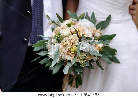 The groom in a suit and the bride in a white dress standing side by side and are holding bouquet of white and cream flowers. Wedding bouquet