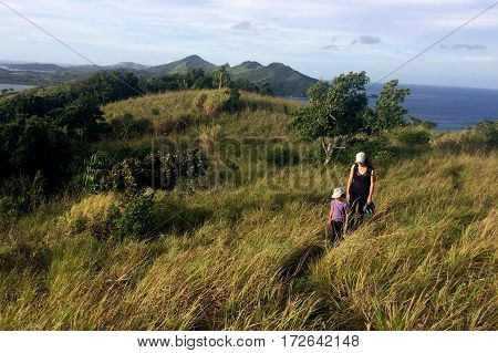 Mother and daughter hiking together on a hill of a tropical island in the Yasawa Islands archipelago in Fiji.