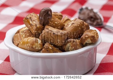 Pretzels in a bowl and chocolate frosting.