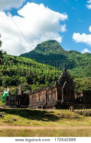 Wat Phu in Southern Laos, view of the lower buildings with the a mountain peak in the distance