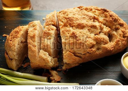 Wooden board with tasty loaf of beer bread on table
