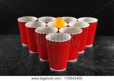 Plastic beer pong cups and ball on dark background
