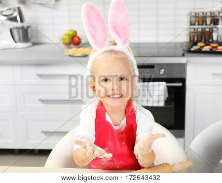 Cute little girl with hands in flour at kitchen