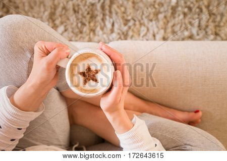 Girl with coffee mug sitting on the sofa indoors. Woman drinking a cup of coffee or tea sitting cozy at home. Relax and rest. Cappuccino with cinnamon star.