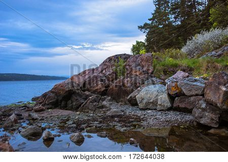 Norwegian beautiful colorful seaside scape with  rocky coast, water reflections and blue sky at the sunset