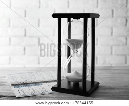 Hourglass with calendar on wooden table