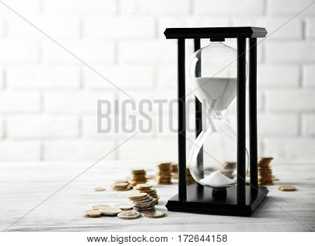 Coins and sandglass on brick wall background