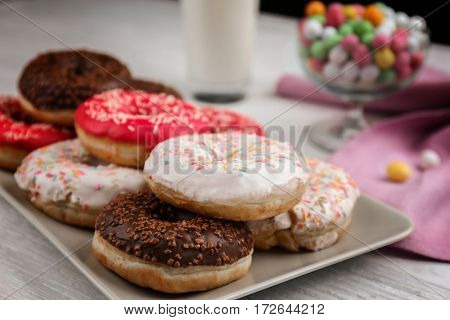 Plate with tasty donuts on table