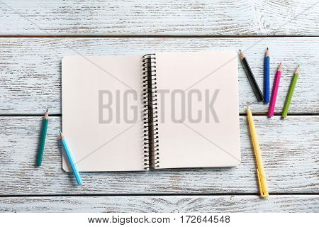 Blank notebook with colorful stationery on wooden table