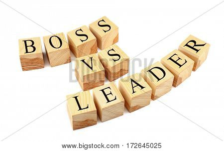 Wooden cubes with text BOSS VS LEADER isolated on white