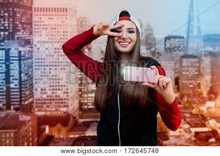 A smiling girl with black eyes. Dressed in black with a red sweater and a cap turned backwards. Itself photographed on a pink smartphone. In the background images of the city at the wallpaper...