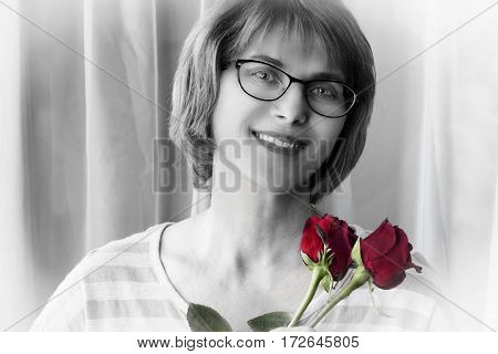 horizontal black and white image of a portrait head shot of a caucasian woman wearing glasses with brown hair holding two red roses close to her cheek.