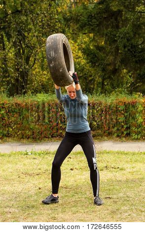 Kiev Ukraine - October 08. 2016. Street workout CrossFit training. Girl raises the tire over his head and forcefully throwing her to the ground.