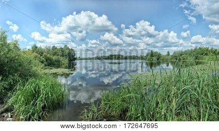 Clouds Reflecting In The Water Of Backwater With Reeds