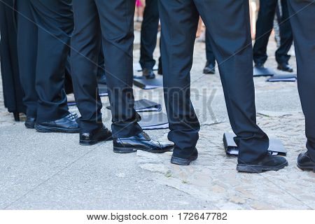 Man's feet in black trousers and black shoes