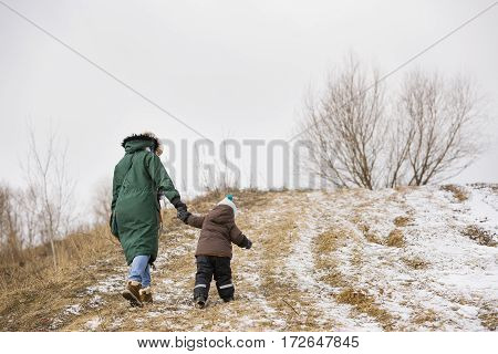 Small toddler boy and his mother walking the mountain trail on a winter day. Woman with little kid walking up the hill on a windy day. Boy following his mom on the valley trail.
