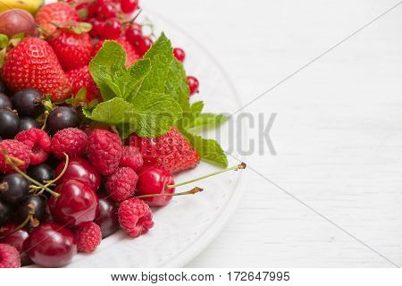Closeup of white plate full of fresh organic berries: strawberries blueberries raspberries gooseberry blackcurrant decorated with mint as summer dessert or snack. Healthy food and eating concept