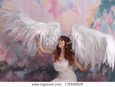 beautiful young model with open angel wings with pink sky background