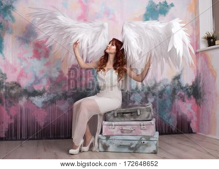 beautiful young model with open angel wings sitting on retro bags in the studio. white background