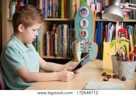 School kid boy sitting at his table and watching tablet pc at home indoors. Child with tablet computer in his room. Studying with tablet computer.