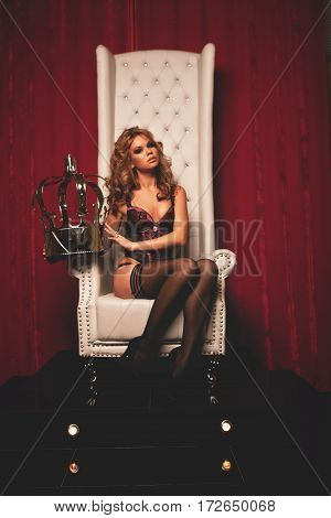 sensual young woman in lingerie sitting on throne
