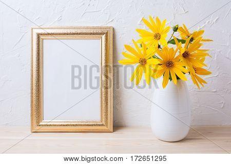 Golden frame mockup with yellow rosinweed flowers in vase. Empty frame mock up for presentation artwork.