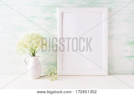 White frame mockup with delicate wild field flowers in pitcher. Empty frame mock up for presentation artwork.