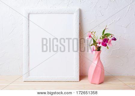 White frame mockup with flowers in swirled pink vase. Empty frame mock up for presentation design.