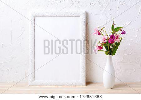 White frame mockup with pink flowers in elegant vase. Empty frame mock up for presentation design.