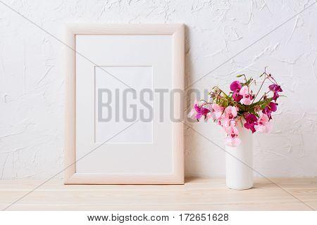 Wooden frame mockup with pink and purple flower bouquet. Empty frame mock up for presentation design.