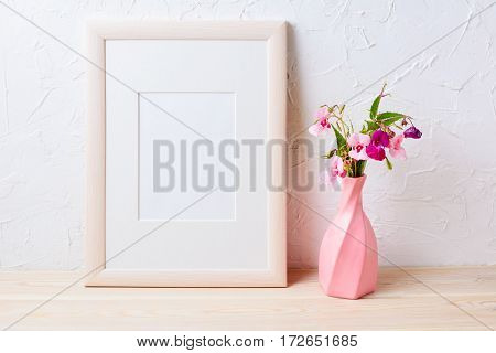 Wooden frame mockup with purple wildflowers in pink vase. Empty frame mock up for presentation design.