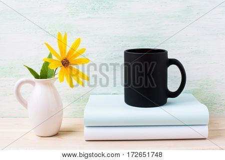 Black coffee mug mockup with yellow rosinweed flowers in pitcher. Empty mug mock up for brand promotion.