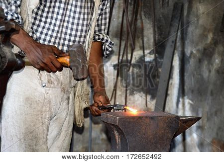 colonial village blacksmith working with hammer away