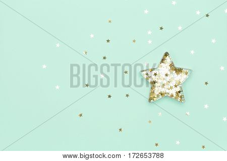 Christmas star made with mold for the cookies and gold sparkling stars on blue background. Flat lay. Holidays and Christmas concept