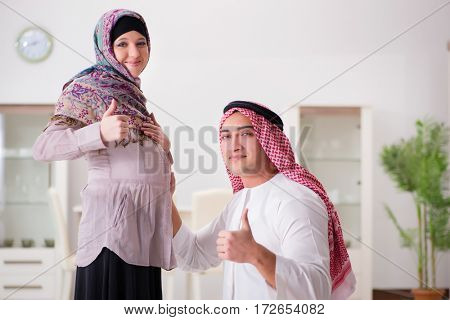 Young arab muslim family with pregnant wife expecting baby