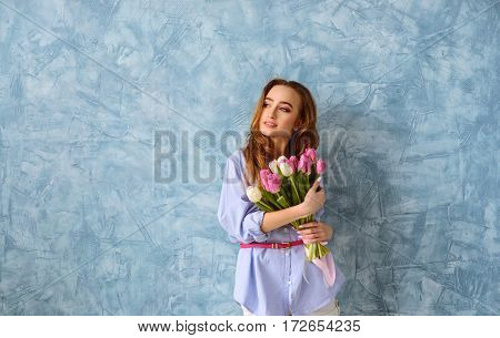 pretty young woman with bouquet of tulips on the blue wall background. Wide shot with copy space