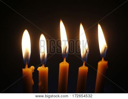 Five Burning Wax Candles On Black Background