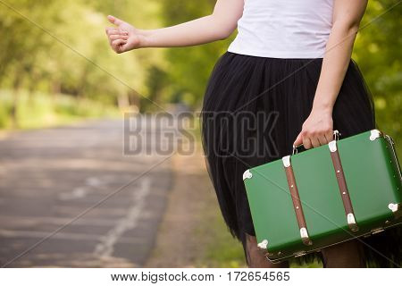 A young girl in a white tank top and black fluffy skirt catching a car on the countryside road. Traveling with a green retro suitcase. Car drive. Catching a taxi in the park outdoor.